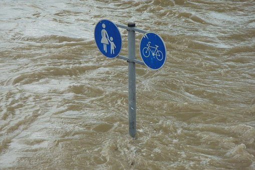 traffic sign of families and bikes crossing surrounded by floods